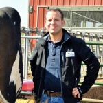 Maurice Kaul outside on farm next to cow