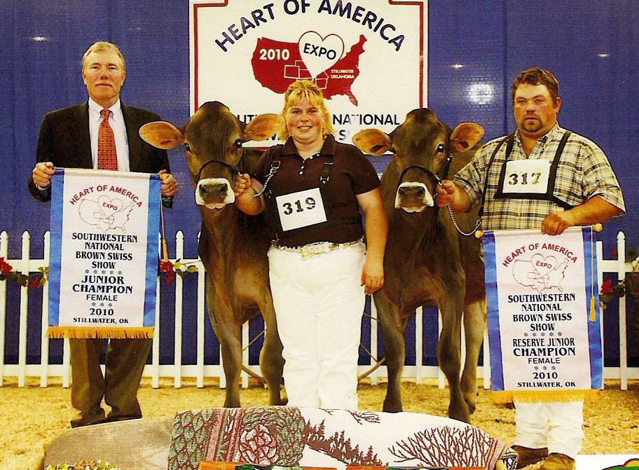 Tammy Voegeli and two champion cows and two men